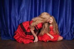 Mutter und Tochter sind beleidigt sitzend und auf dem Boden Mutter versucht, Frieden und Freundschaft mit dem Kind herzustellen stockbild