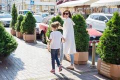 Mutter und Tochter sind das Händchenhalten und gehen entlang die Stadtstraße stockfoto