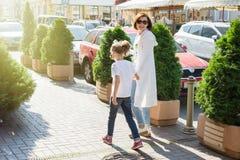 Mutter und Tochter sind das Händchenhalten und gehen entlang das Stadt stree Lizenzfreie Stockfotografie