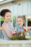 Mutter und Tochter sind an den Blumen Lizenzfreies Stockbild