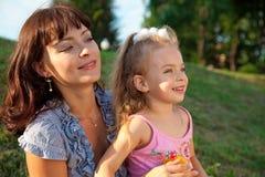 Mutter und Tochter sitzen auf dem Gras Stockbild