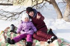 Mutter und Tochter sitzen auf einem Plaid im Schnee im Winter Lizenzfreies Stockfoto