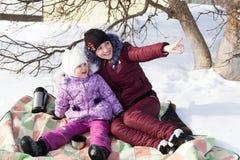 Mutter und Tochter sitzen auf einem Plaid im Schnee im Winter Lizenzfreie Stockfotos
