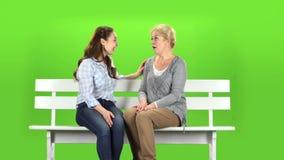 Mutter und Tochter sitzen auf einer Bank Grüner Bildschirm stock footage