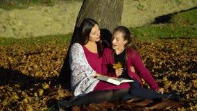 Mutter und Tochter sitzen unter einem Baum und lesen ein Buch Sie sprechen freundlich Mutter und Tochter im Herbstwald sind sie stock video footage
