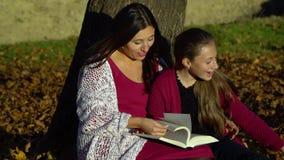 Mutter und Tochter sitzen unter einem Baum und lesen ein Buch Sie sprechen freundlich Mutter und Tochter im Herbstwald sind sie stock video