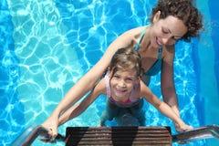 Mutter und Tochter stehen auf Treppen im Pool Stockfotografie