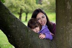 Mutter und Tochter streicheln, wie sie auf einem Baum stillstehen Lizenzfreies Stockfoto