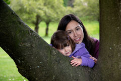 Mutter und Tochter streicheln, wie sie auf einem Baum stillstehen Lizenzfreie Stockfotos