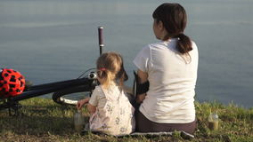 Mutter und Tochter trinken ein grünes Cocktail, das auf dem Ufer des Teichs sitzt stock footage