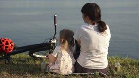 Mutter und Tochter trinken ein grünes Cocktail, das auf dem Ufer des Teichs sitzt stock video