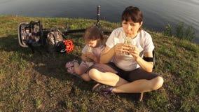 Mutter und Tochter trinken ein grünes Cocktail, das auf dem Ufer des Teichs sitzt stock video footage