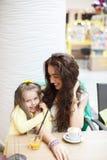 Mutter und Tochter trinken Kaffee und Saft in einem Café Lizenzfreies Stockbild