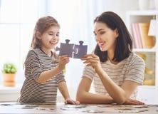 Mutter und Tochter tun Puzzlespiele Stockbilder