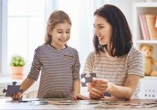 Mutter und Tochter tun Puzzlespiele Stockfotografie
