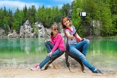 Mutter und Tochter tun Selfe auf Ufer von See Stockbilder
