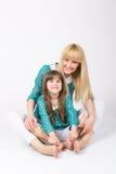 Mutter und Tochter umarmen sitzende tragende zusammenpassende Ausstattung Stockfotografie