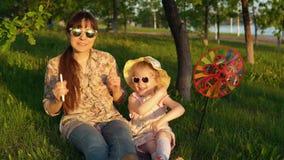 Mutter und Tochter verbringen glücklich die Zeit, die zusammen auf dem Gras bei Sonnenuntergang spielt stock video footage