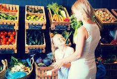 Mutter und Tochter wählen Gemüse im Gemüseshop Lizenzfreie Stockbilder