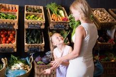 Mutter und Tochter wählen Gemüse im Gemüseshop Stockbilder