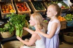 Mutter und Tochter wählen Gemüse im Gemüseshop Stockfoto