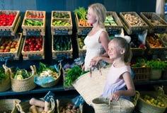 Mutter und Tochter wählen Gemüse im Gemüseshop Lizenzfreies Stockbild
