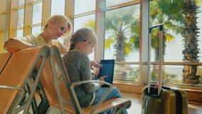 Mutter und Tochter warten auf den Flug am Flughafenabfertigungsgebäude Ein Mädchen benutzt eine Tablette, eine junge Frau sitzt stock footage