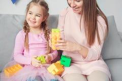 Mutter und Tochter weekend mit Spielzeugziegelsteinen zusammen zu Hause spielen Stockbilder