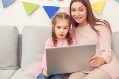 Mutter und Tochter weekend unter Verwendung des Laptops zusammen zu Hause sitzen Stockfotografie