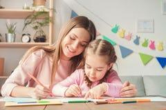 Mutter und Tochter weekend Zeichnung zusammen zu Hause, umarmend Lizenzfreies Stockbild