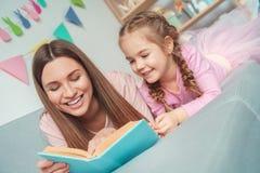 Mutter und Tochter weekend zusammen zu Hause auf dem Sofalesebuchlachen Lizenzfreie Stockbilder