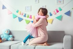 Mutter und Tochter weekend zusammen zu Hause auf dem Sofaumarmen Stockbild
