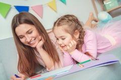 Mutter und Tochter weekend zusammen zu Hause auf dem Sofazeichnungslächeln Lizenzfreie Stockfotografie