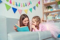 Mutter und Tochter weekend zusammen zu Hause auf Sofalesemärchen Lizenzfreie Stockfotografie