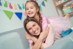 Mutter und Tochter weekend zusammen zu Hause auf Sofamädchen auf Mutter ` s hinterem Lachen Lizenzfreie Stockbilder