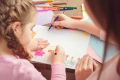 Mutter und Tochter weekend zusammen zu Hause Bildungskonzeptrückseitenansichtnahaufnahme-Zeichnungsblumen Lizenzfreies Stockfoto