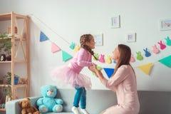 Mutter und Tochter weekend zusammen zu Hause das Mädchen, das auf Sofa springt Stockfotos