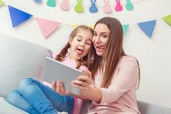 Mutter und Tochter weekend zusammen zu Hause das Sitzen, die digitale Tablette halten, die selfie Fotos macht Lizenzfreie Stockfotos
