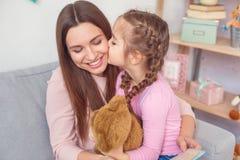 Mutter und Tochter weekend zusammen zu Hause das sitzende Mädchen, das den Teddybären hält, der Mutter küsst Stockfotos
