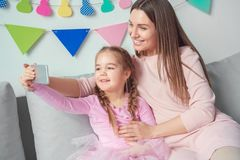 Mutter und Tochter weekend zusammen zu Hause das sitzende Mädchen, das selfie Fotos macht Stockbilder