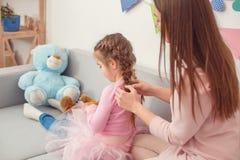 Mutter und Tochter weekend zusammen zu Hause die sitzende Mutter, die Frisur macht Lizenzfreie Stockbilder