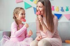 Mutter und Tochter weekend zusammen zu Hause sitzen, Lutscher essend Stockfotos