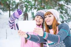 Mutter und Tochter werden in einem Winterwald fotografiert lizenzfreies stockbild