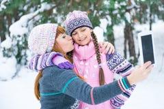 Mutter und Tochter werden in einem Winterwald fotografiert lizenzfreie stockbilder