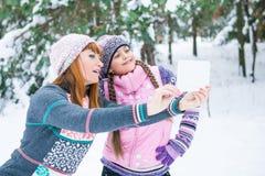 Mutter und Tochter werden in einem Winterwald fotografiert stockfotografie