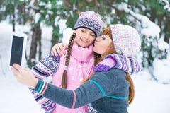 Mutter und Tochter werden in einem Winterwald fotografiert lizenzfreie stockfotografie
