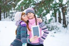 Mutter und Tochter werden in einem Winterwald fotografiert stockfoto