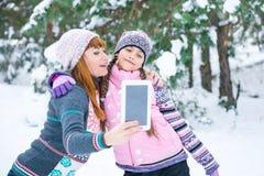 Mutter und Tochter werden in einem Winterwald fotografiert lizenzfreie stockfotos