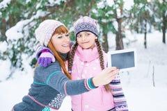 Mutter und Tochter werden in einem Winterwald fotografiert lizenzfreies stockfoto
