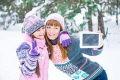 Mutter und Tochter werden in einem Winterwald fotografiert stockfotos